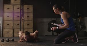 Cross training at a gym. Front view of a shirtless athletic Caucasian man cross training at a gym doing press ups, while a Caucasian female trainer with a stock video