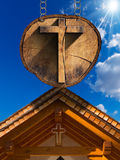 Cross on Tree Trunk with Wooden Church Royalty Free Stock Image