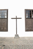 Cross Between two Windows. A very simple and plain wooden cross attached to the outside wall of a monastery in the town of Teguise, Lanzarote Royalty Free Stock Photography
