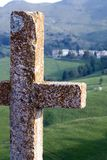 Cross with a view. A small worn cross overlooks a small village in Northern Italy stock image