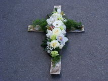 Cross of white wood and flowers. Cross made of wood, decorated with white roses, orchids and tulips, green carnations and asparagus Royalty Free Stock Photography