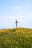 Cross. Wooden Cross on a hill, field flowers surround Stock Photography