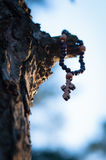 Cross in the woods hanging from a tree Royalty Free Stock Photography