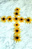 The cross of yellow flowers. On a marble table Royalty Free Stock Photos