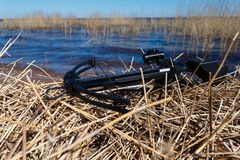 The crossbow on the dry grass. On the background of lake water Royalty Free Stock Photography
