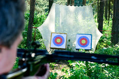 Crossbow shooting. Man aiming crossbow at targets in summer forest Royalty Free Stock Photo