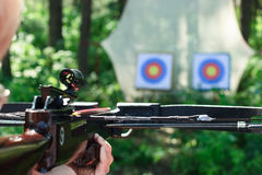 Crossbow shooting. Man aiming crossbow at targets in summer forest Royalty Free Stock Image