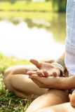 Crossed arms are put on the legs of the girl in meditation. Royalty Free Stock Photography