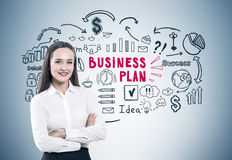 Crossed arms woman and business plan gray. Close up Stock Image