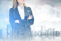 Crossed arms woman and a city. Double exposure of an unrecognizable crossed arms businesswoman standing against a city panorama, mock up stock photos