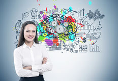 Crossed arms woman and gear brain. Portrait of a young smiling businesswoman standing with crossed arms near a gray wall with a colorful brain sketch, cogs on stock image