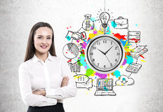 Crossed arms woman and time management. Portrait of a cheerful young businesswoman standing with crossed arms and looking at you. Concrete wall background with a Stock Photo