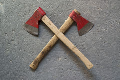 Crossed axes. Two crossed axes on a background of concrete Stock Image