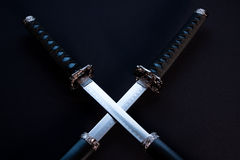 Crossed blades on black background. Stock Images