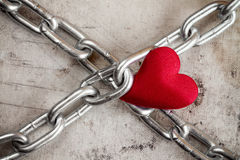 Crossed chains with red heart Stock Images