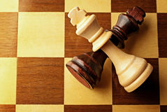 Crossed chess pieces on a chessboard Royalty Free Stock Images