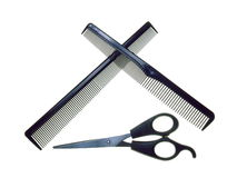 Crossed Combs with Scissors. Two combs and a pair of hair-trimming scissors - isolated over pure white Royalty Free Stock Photo
