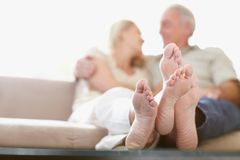 Crossed feet of a couple sitting together at home Royalty Free Stock Photo