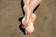 Crossed feet in sand Stock Photo