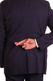 Crossed fingers behind back. Businessman in dark suit with crossed fingers behind his back Royalty Free Stock Photos