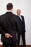 Crossed Fingers At Handshake. As a symbol of breach of contract Royalty Free Stock Photography