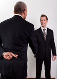 Crossed Fingers At Handshake. As a symbol of breach of contract Stock Photography