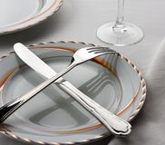 Crossed fork and knife on the plate Royalty Free Stock Photography