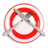 Crossed fork and knife on a plate Royalty Free Stock Photo
