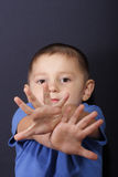 Crossed hands. Boy in blue shirt with crossed hands over dark background Royalty Free Stock Photos