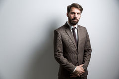 Crossed hands grey wall. Bearded male dressed in suit with crossed hands standing against grey wall. Mock up Royalty Free Stock Photos