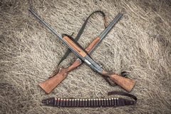 Crossed hunting shotguns with ammunition belt on dry rural field as hunting background Stock Photos