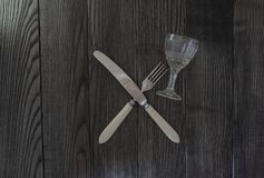 Crossed knife fork and glass Royalty Free Stock Photo