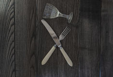 Crossed knife fork and glass Royalty Free Stock Photography