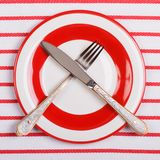 Crossed knife and fork on a red plate on striped tablecloth Stock Photos