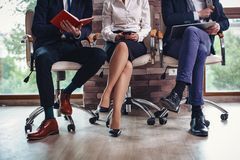 Crossed legs of business people sitting in a row stock images