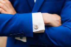 Crossed man`s hands on his chest in a blue jacket. Cuff links fr. Om the watch mechanism stock photos