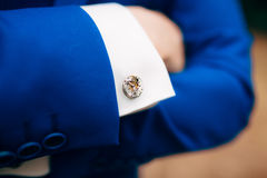Crossed man`s hands on his chest in a blue jacket. Cuff links fr. Om the watch mechanism royalty free stock photography