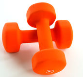 Crossed orange dumbells. Orange dumbells crossed over each other with the number 7 on the front of one of the dumbells stock photo