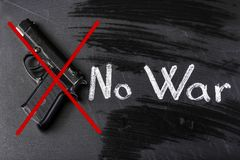 No war. Crossed out gun on the board near to the inscription there is no war stock images