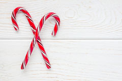 Crossed peppermint candy canes on white wooden background, copy space Stock Image