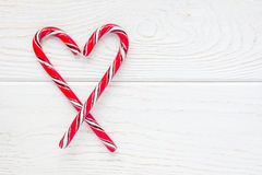 Crossed peppermint candy canes on white wooden background, copy space Royalty Free Stock Image