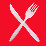 Crossed plastic knife and fork Stock Photo