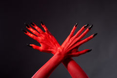 Crossed red devil hands with black nails. Studio shot on black background stock photos