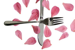 Crossed silver fork and knife with rose petals Royalty Free Stock Photography