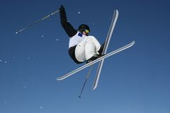 Crossed Skis. Skier jumping with crossed skis with a blue sky background Stock Image