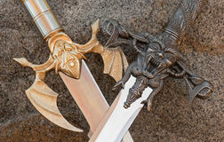 Crossed swords medieval with demons. Metal gold and silver swords showing decorative handles stock photo