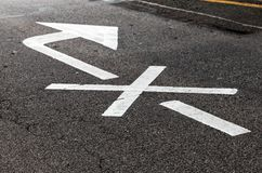 Crossed white arrow, road marking stock photography