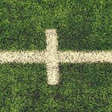 Crossed white lines on outdoor football playground. Detail of lines in a soccer field. Plastic grass and finely ground b Royalty Free Stock Photo