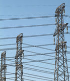 Crossed wires. Electricty power pylons or towers with a criss-sross pattern of wires stock photography