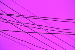 Crossed Wires over a dark lavender background. This pattern of an array of crossed wires combines direction with misdirection Stock Photo